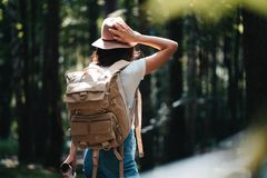 有站立在森林年轻行家女孩的背包和帽子的英俊的旅客妇女走在日落的树中 免版税库存图片