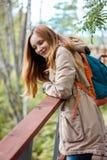 有站立在森林桥梁和s的红色长的头发的女孩旅客 库存图片