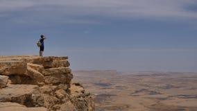有站立在沙漠山岩石峭壁边缘的背包的人 免版税库存照片