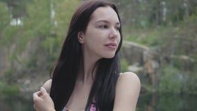 有站立在河或湖附近的长的黑色头发的画象俏丽的年轻女人 在城市之外的可爱的女孩步行 股票视频