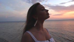 有站立在海滩的外形和观看对海的棕色头发的年轻长发青少年的女孩在一个夏天晚上 股票录像