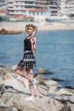 有站立在海的小的猪尾的白肤金发的妇女晃动 免版税图库摄影