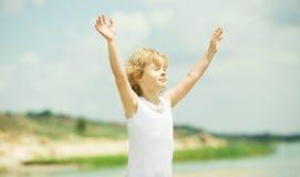 有站立在海附近的被举的胳膊的愉快的孩子 免版税库存图片