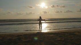 有站立在海洋海滩的围巾的年轻愉快的妇女在日落 享受女孩夏天 在比基尼泳装的女性剪影 股票视频