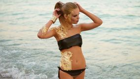 有站立在海滩的水中的专业金黄构成的美丽的妇女,看在照相机 性感 影视素材