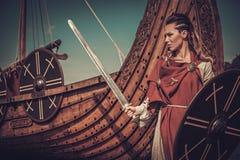 有站立在海滨的Drakkar附近的剑和盾的北欧海盗妇女 免版税库存图片