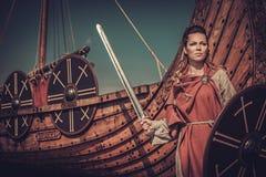 有站立在海滨的Drakkar附近的剑和盾的北欧海盗妇女 免版税库存照片