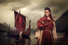 有站立在海滨的Drakkar附近的剑和盾的北欧海盗妇女 库存图片