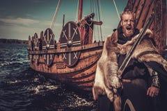 有站立在海滨的Drakkar附近的剑和盾的北欧海盗战士 免版税图库摄影