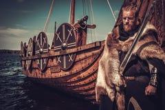 有站立在海滨的Drakkar附近的剑和盾的北欧海盗战士 库存照片