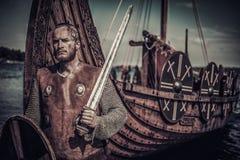 有站立在海滨的Drakkar附近的剑和盾的北欧海盗战士 免版税库存照片