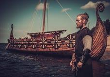 有站立在海滨的Drakkar附近的剑的北欧海盗战士 免版税图库摄影