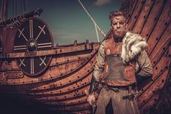 有站立在海滨的Drakkar附近的轴的北欧海盗战士 库存图片