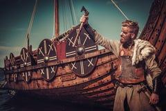 有站立在海滨的Drakkar附近的轴的北欧海盗战士 免版税库存图片
