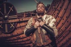 有站立在海滨的Drakkar附近的轴的北欧海盗战士 免版税库存照片