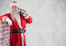 有站立在烟囱旁边的礼物大袋的愉快的圣诞老人 图库摄影
