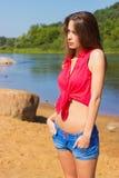 有站立在牛仔布的长的黑发的性感的美丽的女孩在海滩短缺在水附近在一个晴天 免版税图库摄影