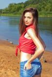有站立在牛仔布的长的黑发的性感的美丽的女孩在海滩短缺在水附近在一个晴天 免版税库存照片