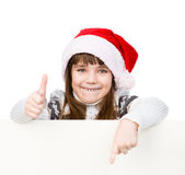 有站立在白板后的圣诞老人帽子的美丽的女孩 查出在白色 免版税库存照片