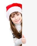有站立在白板后的圣诞老人帽子的美丽的女孩 背景查出的白色 免版税库存图片