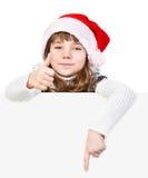 有站立在白板后的圣诞老人帽子的美丽的女孩 免版税库存照片