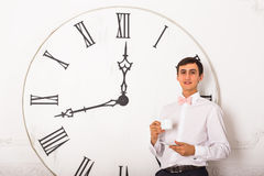 有站立在白色墙壁上的一个大时钟旁边的茶的人 库存照片