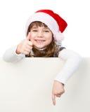 有站立在白色的白板后的圣诞老人帽子的美丽的女孩 库存图片