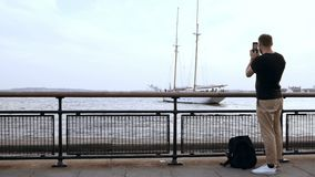 有站立在码头和拍汽船的照片的在智能手机的背包的年轻英俊的人 影视素材