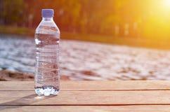 有站立在码头的纯净的泉水的瓶在水附近 免版税库存图片
