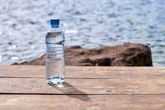 有站立在码头的纯净的泉水的瓶在水附近 库存照片