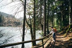 有站立在窄路,在被包围的山湖的银行的小道路的橙色背包的旅游女孩  免版税库存照片