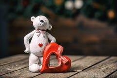 有站立在老木背景的心脏的白熊玩偶 在红色玫瑰色华伦泰白色的概念重点 免版税库存图片