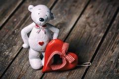 有站立在老木背景的心脏的白熊玩偶 在红色玫瑰色华伦泰白色的概念重点 免版税库存照片