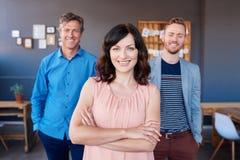 有站立在背景中的微笑的同事的确信的年轻女实业家 免版税库存图片