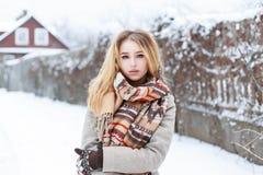 有站立在背景的被编织的围巾的美丽的女孩  库存照片