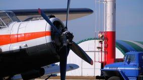有站立在航空器停车处的推进器的小飞机在一个小机场的飞机棚附近 影视素材