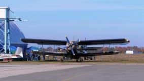 有站立在航空器停车处的转动的推进器的小飞机在一个小机场的飞机棚附近 股票录像