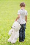 有站立在草甸的玩具熊的哀伤的孤独的男孩 看的孩子下来 回到视图 悲伤,恐惧,寂寞概念 免版税库存照片