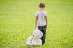有站立在草甸的玩具熊的哀伤的孩子 看的孩子下来 回到视图 库存照片