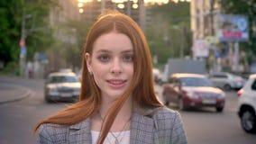 有站立在街道和看在照相机的姜头发的年轻迷人的妇女在日落,微笑,汽车交通期间  影视素材