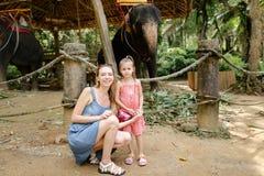 有站立在被驯服的和被栓的大象附近的小女儿的年轻母亲 免版税库存图片