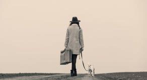 有站立在路的手提箱和狗的少妇 免版税库存图片