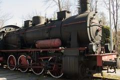 有站立在路轨的红色轮子的一个老黑葡萄酒减速火箭的机车 免版税库存图片