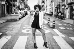 有站立在都市backgrou的非洲的发型的年轻黑人妇女 免版税库存图片