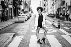 有站立在都市backgrou的非洲的发型的年轻黑人妇女 库存图片