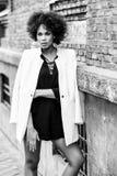 有站立在都市backgrou的非洲的发型的年轻黑人妇女 免版税库存照片