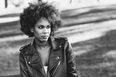有站立在都市backgrou的非洲的发型的年轻黑人妇女 图库摄影