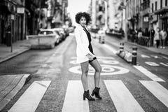 有站立在都市backgrou的非洲的发型的年轻黑人妇女 库存照片