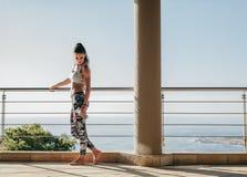 有站立在阳台上的强健的身体的美丽的妇女 免版税库存照片
