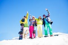 有站立在雪的雪板的四个朋友 图库摄影